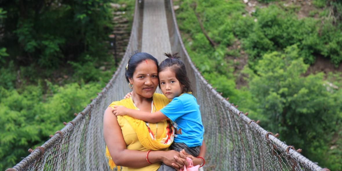 Frau mit Kind auf Hängebrücke